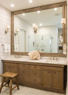Beautiful white and brown bathroom boasts a rustic stool placed on an tan rug in front of a brown dual washstand fitted with a white marble countertop holding two sinks with satin nickel vintage faucets beneath a large brown vanity mirror lit by satin nickel sconces mounted to white shiplap trim.