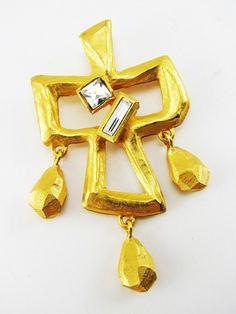 Винтажная брошь/кулон с подвесками от CHRISTIAN LACROIX! Сразу видно, чьих великих рук дело. Присущая всем работам этого дизайнера и любимая мною художественная ассиметрия и нездешняя сумасшедшинка. Толстый металл  нарочито грубой обработки и с  эффектом мятости, будто вытесанные из кусочков золотых слитков подвески вносят элемент некой легкомысленности. Два крупных кристалла завершают эффектный кристалла. Клеймо «CHRISTIAN LACROIX  CL Made in France». Размер: 7,3 см.