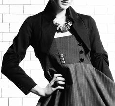 The Cropped Jacket is a short bolero-style jacket with long sleeves. The collar, reworked from an inverted men's suit jacket collar, sits high at the back of the neck and then runs to under the arm. The sleeves feature accordian stitching detail at the elbows and cuff button detail at the wrists.