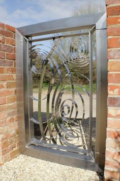 Contemporary stainless steel automated gates. Walk through side gate.