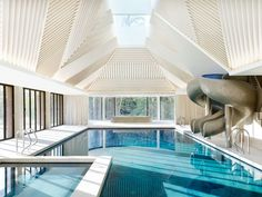 A triangular skylight crowns Twin corkscrewing slides; the walls and floor are clad in botticino marble, while the pool is lined with book-matched Azul Macauba quartzite.