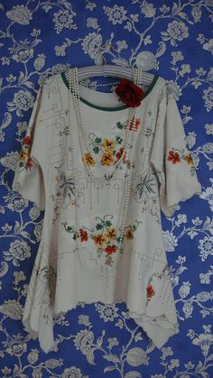 Stunning layering tunic top fashioned from a winter white vintage cotton linen tablecloth with outstanding hand embroidery. This beauty has a scooped neckline edged in green to match the fabulous embroidery. The sleeves are 3/4 in length with added embroidery. The tunic has been cut