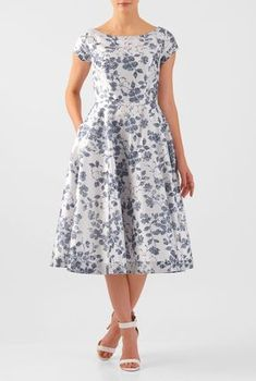 Our fit-and-flare dress is cut from polydupioni in a mesmerizing floral print with trapunto stitch banding at the boat neck, cuffs and hemline.