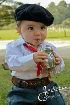 Little boy dressed up as a gaucho drinking mate (typical Argentinian infusion)