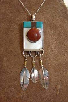 Red coral mounted on mother o pearl, turquoise & ironwood... and attached eagle feathers with brass wrappings