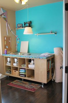Cutting table Expedit - Sewing Room. Redo by Melanie Dramatic, via Flickr  Bolt storage, solid side nice to scissor/ ruler caddy and like the wheels.