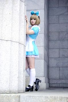 Cosplay girl in blue dress, head bow, and white socks