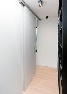 Schuifdeur van vloer tot plafond met een aluminium rail die tegen het plafond verankerd zit. Geen zichtbare geleiding op de vloer.