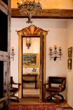 Iberian influence: Love the wall sconces, door frame and chandelier... a  little Cali-Mediterranean interchange going on here, I think