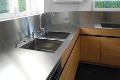 Küche mit Edelstahlabdeckung, Fronten in Lärche horizontal furniert mit durchgehendem Furnierbild.