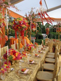 Tented outdoor reception featuring candelabras, hanging floral arrangements and gold chandelier