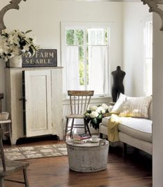 The owner of this light-filled living room found imaginative applications for vintage finds—she turned a 19th-century wooden tub into a coffee table and utilized an antique checkerboard as a unique piece of art.   - CountryLiving.com