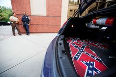 Confederate flags sit in the back of a police car - AP Photo/David Goldman