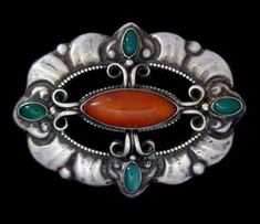 SKONVIRKE BROOCH A silver brooch set with a amber and green agates. Denmark. Circa 1915.   Marked 'HF' and '830S.' Size: Height 4 cm. Width 5 cm.