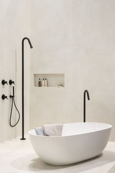 Bathtub with detached bathroom faucet, black taps in neutral bathroom