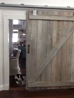Barn door made from reclaimed barn wood white washed with minwax pickling stain. Tractor supply rail and hangers. Vintage handle.