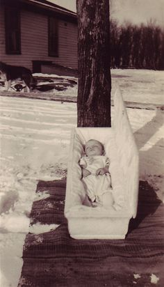 A mid-twentieth century snapshot showing an infant in a white coffin lying in the snow.