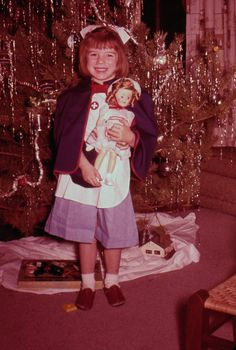 Vintage photo.... Little girl wearing nurse outfit, holding her new doll. c1958