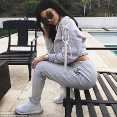 Designer sports:For their filmed lunch, Kylie wore a pair of grey tapered tracksuit pants with a matching sweater which had an oversize shoe lace-like tie on one shoulder