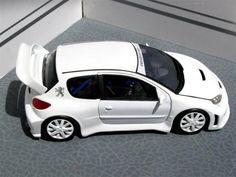 Peugeot 206 WRC 1/18 SOLIDO.  Modifs : - suppression des prises d'air de toit, capot et antennes - prise d'air supplémentaire + une lame sur le parechoc avant - Installation de phares d'antibrouillard - modifs du parechoc arrière pour l'intégration des pots d'échappement - nouveaux bas de caisse - ligne d'échappement complète - modif de l'arceau cage + installation d'un boîtier HKS - Jantes Peugeot RC - Fabrication d'un nouveau pare-brise - peinture blanc brillant - compteurs perso