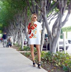 Dani Song wearing a shift dress with stand up collar and floral print design paired with black heeled sandals