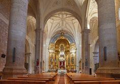 Monumental interior de la iglesia de San Juan Bautista con tres naves a la misma altura y un notable retablo mayor de fines del siglo XVIII que alberga una bella talla gótica de Cristo crucificado
