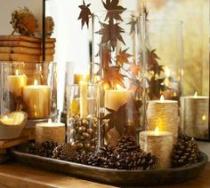 Fall tips decor by Pottery Barn | Create a Fall mantel in 3 easy steps: 1) place flameless candles in glass vessels of varying heights.  2) fill glass with faux or real acorns and leaves (spray paint gold for a gilded touch) 3) set candles in trays with pinecones to complete the look.