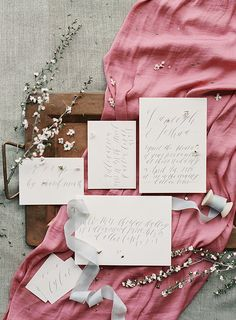 Grey calligraphy wedding invitation on pink silk (Paper goods: Wondrous Whimsy) - Blush, peach & blue spring wedding ideas by Lindsey Brunk (Styling & design) + Lauren Peele (Photography) - via Magnolia Rouge