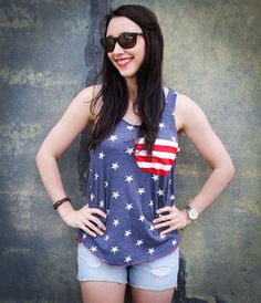 Let your freedom ring in this American Flag pocket tank perfectly on trend this season. Made of so soft Eco-friendly materials and available in sizes S, M, L, and XLYou will love this so-soft eco-heather racerback tank top. This is a Light weight tank which can be worn alone or layered over another tank.This listing is for one heather blue and white stars tank top with a red   white striped slub pocket. Pictured in a size Large. Available in sizes Small-LargeThis top fea...