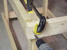 Pre-drilling holes for screws in frame of workbench.