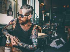 hombre con tatuajes trabajando en un bar