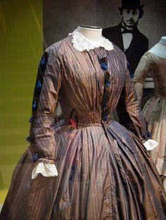 1861-65 striped silk dress with shirred body, double box pleats, tassel trim. Musée de la Mode et de la Dentelle, Brussels. Photo by Cristoph Houbrechts Vanhoorne.
