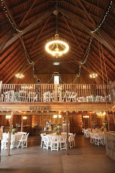 Reception site with tables in a wodden barn and lights suspended over tables and do it in blue and red.