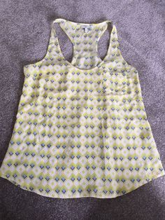 This is a very nice Joie Silk Sleeveless Shirt Women's size medium. The shirt is a geometric design in yellow, white, and blue. All measurements are approximate and taken with the shirt laying flat.