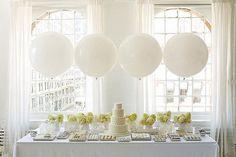 White dessert table with hydrangea flower arrangements.
