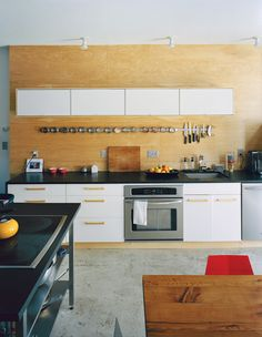 Concrete floors and an Ikea kitchen and spice rack make for an affordable, cleanly geometric aesthetic at the back of the bottom floor. The appliances are by Frigidaire, and the black countertops are sealed with Eco Tuff by Eco Procote.  Photo by: Mark Mahaney