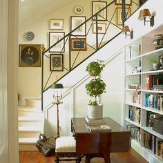 Really lovely combination foyer, stairway, library, and gallery by Scott Yetman Designs. Love the contrast of the gorgeous iron balustrade and iron/leather sconces with the light buttery walls,. Entry Stairs, Entry Foyer, Basement Entrance, Stairway Gallery Wall, Stair Gallery, Gallery Walls, Library Lighting, White Stairs, Foyer Decorating