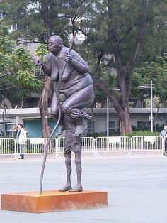 """Survival of the Fattest is a sculpture of a small starving African boy, carrying Lady Justice, an enormous obese European woman who is a symbol of the rich world. Survival of the Fattest is 11 feet, 3.5 meters tall sculpture was created by Jens Galschiøt in collaboration with his colleague Lars Calmar. On the sculpture there is an inscription, which states: """"I'm sitting on the back of a man. He is sinking under the burden. I would do anything to help him. Except stepping down from hi..."""