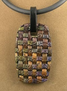 a tag art pendant. I smeared the inks on black clay in a rainbow effect and let dry over night. I cut the clay into strips and made a basket weave. I used a metal embossing plate to add texture. The bail is black clay.