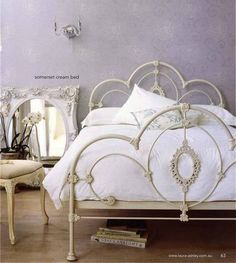 OH! I love this cream iron bed and white antique inspired mirror. Forget it, I love the whole thing.
