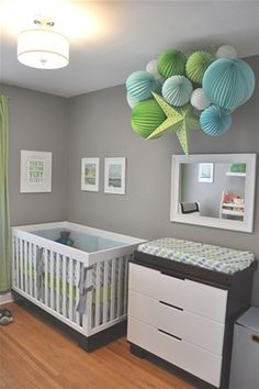 This room is all about the clustered paper lanterns hanging from the ceiling. The trend of hanging large items in lieu of a typical mobile is really adorable, and I like that this one isn't directly above the crib where one might otherwise be concerned about baby's safety. Muted grey walls are a great backdrop for this colorful ceiling decoration and it's mesmerizing!