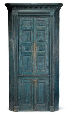 Blue-painted paneled corner cupboard pennsylvania or new jersey, circa 1800 One piece cupboard with projecting molded cornice above four paneled doors opening to a shelved interior, framed by molded pilasters and carved corner blocks. H: 84 in. W: 42 in.