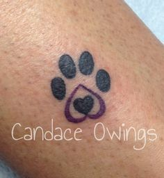 A memorial tattoo I did for her dog that ran away of a par print with a heart and purple because the dog had a purple leash.