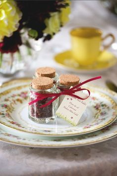 A trio of artisan salts, including the Halen Mon Gold, Cabernet, and Fleur de Sel de I'lle de Re varieties, are packaged in individual glass jars, each one corked and tied with burgundy silk ribbon