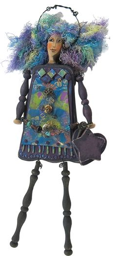 Meta Strick combines bits of wood, wire, beads & yarn on her art dolls. Then she dresses them in polymer which she paints. Often the dolls carry inspirational messages.