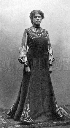 1903 German 'New Artistic Reform Dress' designed by Elizabeth Winterwerber. Princess line pinafore with gored skirt and Art Nouveau motifs worn with a high-necked blouse.