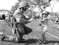 US Marine, Staff Sergeant Federico Claveria who was a Combat photographer with the Amphibous Corps, stops by a barbed wire fence to offer sweets to a Japanese child held in an Internment Camp on the island of Tinian in the Mariana Islands. Colorized Historical Photos, Historical Pictures, Tiger Ii, Barbed Wire Fencing, Wire Fence, Culture G, Staff Sergeant, Japanese Boy, Go Camping