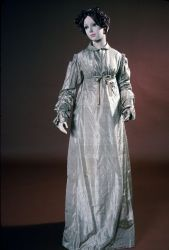 """OSV - Tan Silk """"Round Gown"""" - ca. 1795 to 1800 - Silk - Open at front waist with bodice and skirt separated. High neck collar edged with a self-gathered whipped edging.  Back is pleated above and below waist. Attached belt ties in front. Side front bodices are gathered at bottom with drawstring. Skirt front opens at sides three inches down. Skirt flares slightly from waist to hem. Single half inch tuck at hem."""
