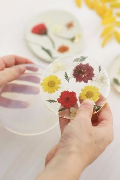 Add a splash of color to your home (and protect against pesky spills and scratches) with these easy-to-make pressed-flower coasters.