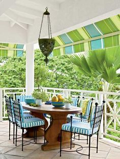 Bold, striped awnings shield from the afternoon sun, and iron chairs outfitted in complementary cushions invite guests to have a seat.